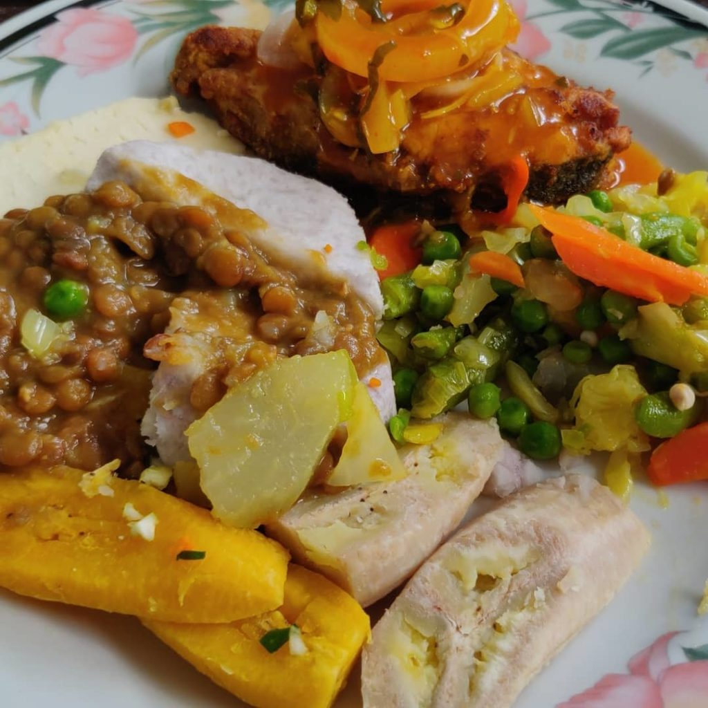 delicious plate of saint lucian food with fish and creole sauce and a variety of ground provisions such as greenfig, plantain, dasheen, yam